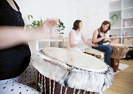 Frauen im Stuhlkreis mit Trommeln