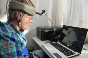 Ein Mann sitzt vor einem Laptop und tippt mit einem Stift, der an einem Gestellt auf seinem Kopf befestigt ist, auf die Tastatur.