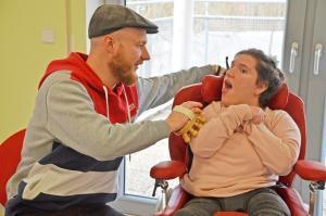 Ein Mann massiert eine junge Frau im Rollstuhl mit einem Massagegerät an seiner Hand.