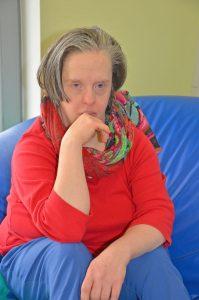 Eine Frau Sitzt auf einem blauen Sitzsack und schaut in die Kamera.