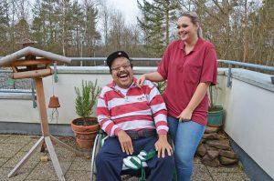 Ein Mann sitzt in seinem Rollstuhl auf der Terrasse, seine Assistentin leistet ihm Gesellschaft.