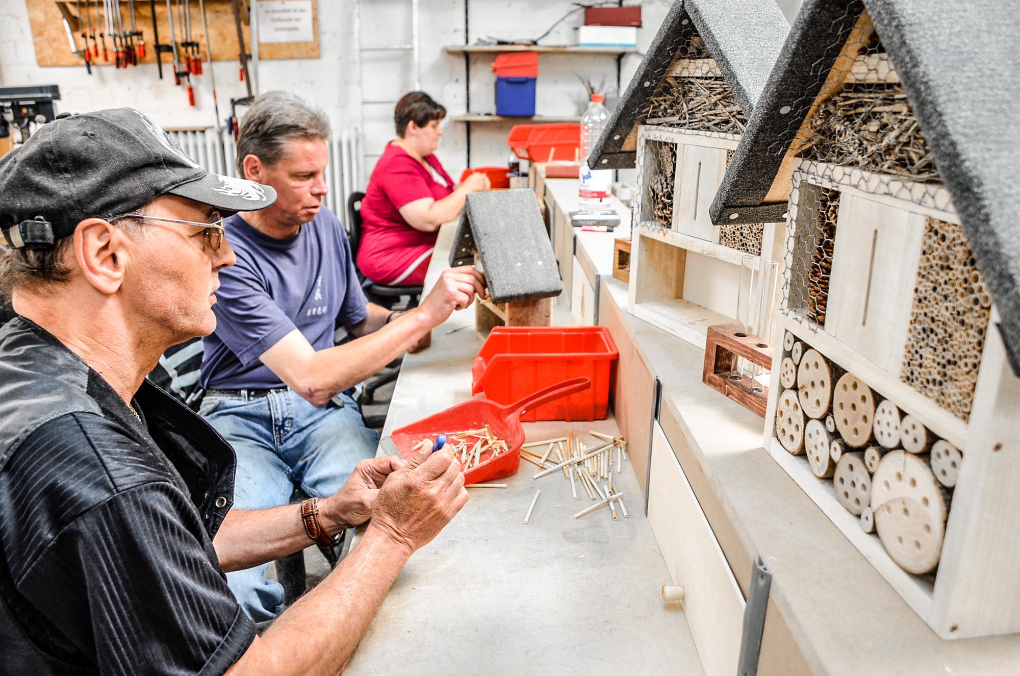 Menschen bauen Vogelhäuser in einer Werkstatt
