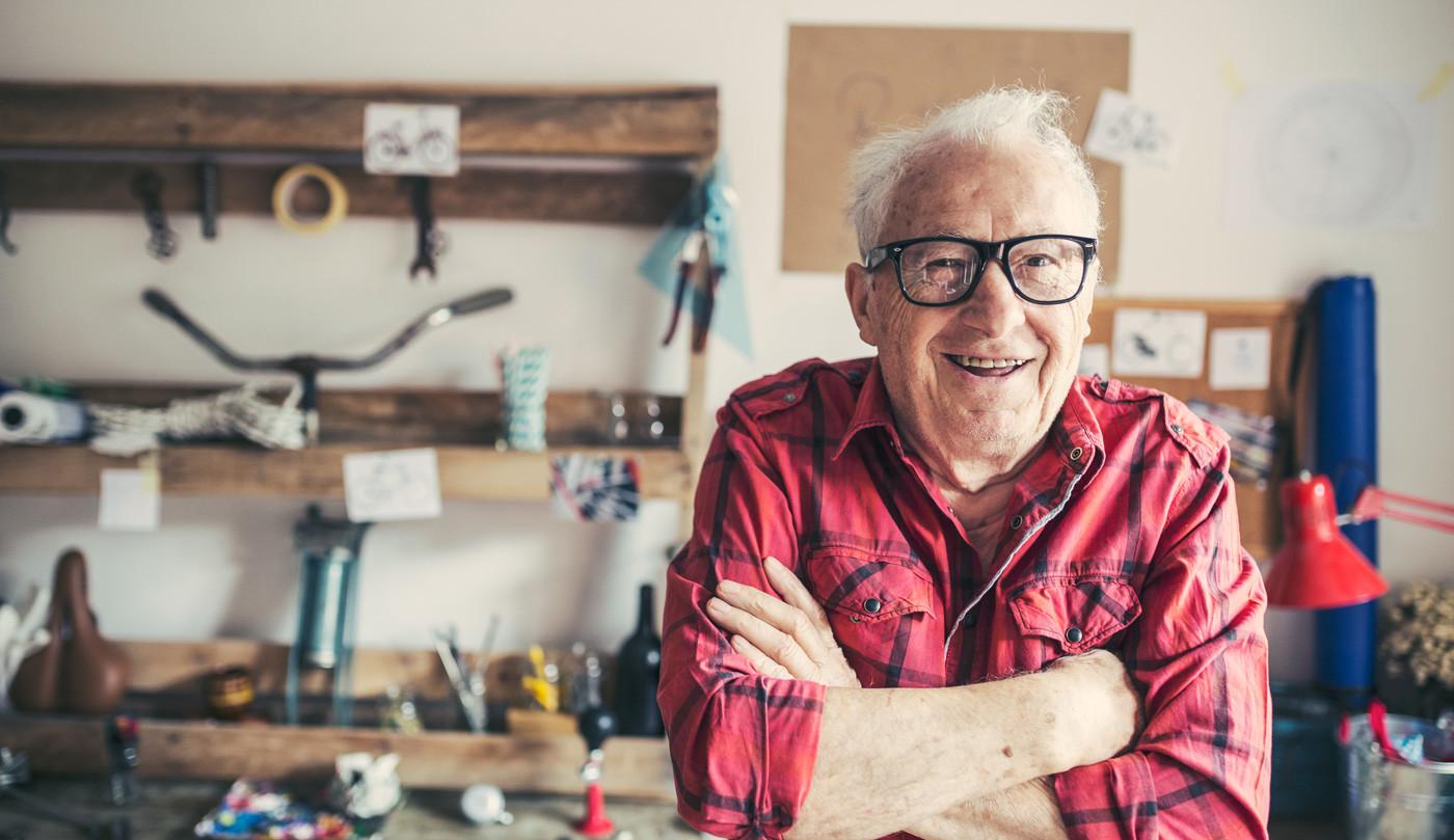 glücklicher alter Mann in seiner Werkstatt