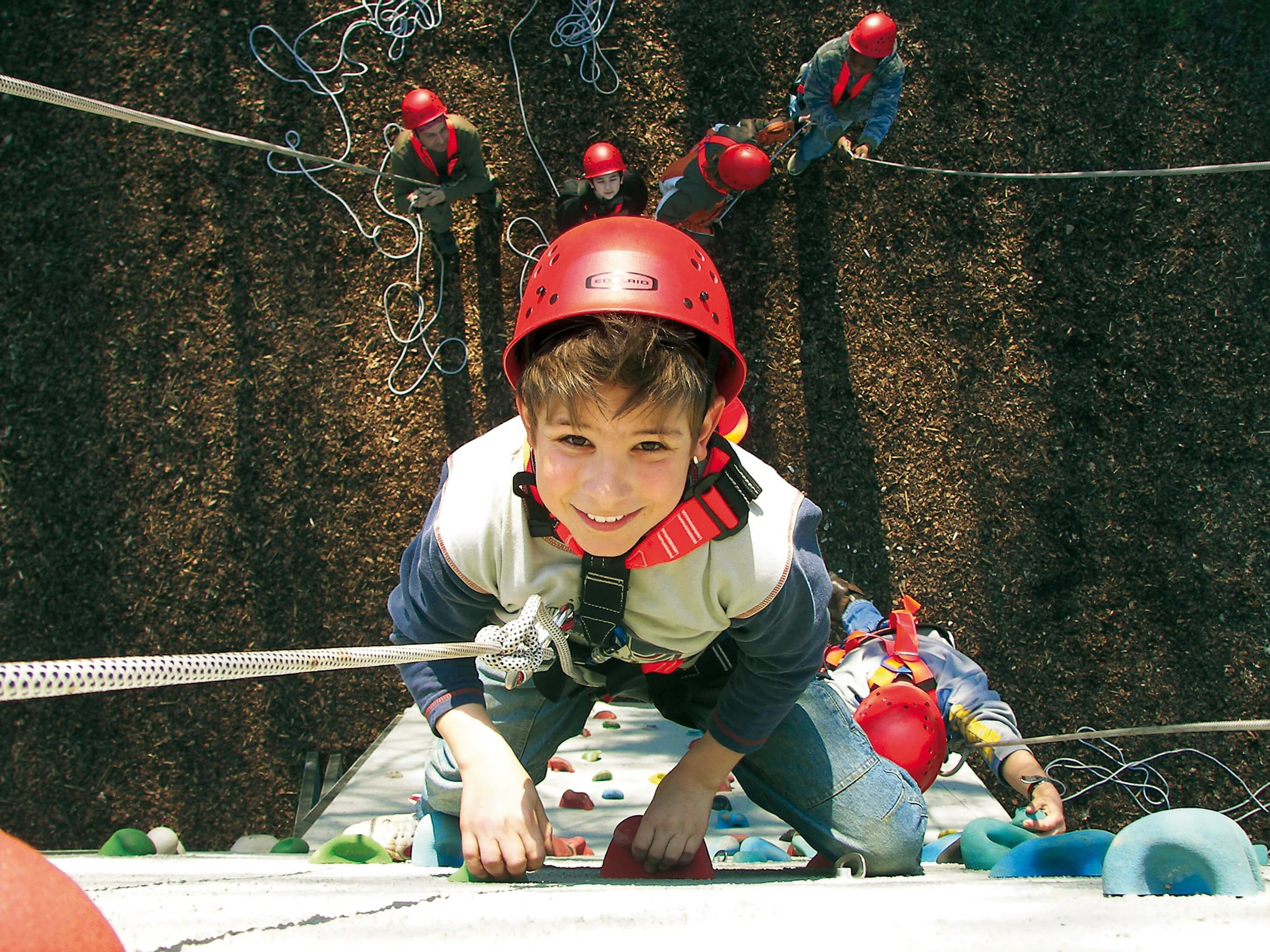 Junge klettert an einer Kletterwand