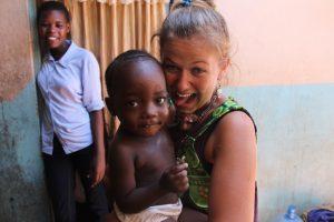 Luisa Frick hält ein schwarzes Baby auf dem Arm. Im Hintergrund steht eine schwarze Frau, die lächelt.