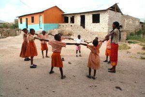 Acht schwarze Kinder und ein Erwachsener halten sich an den Händen und stehen im Kreis. Im Hintergrund ist das neue Waisenhaus zu sehen.