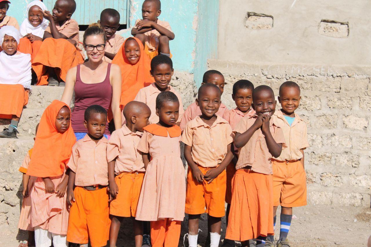 Auf dem Bild ist eine weiße junge Frau zu sehen, die mit schwarzen Jungen und Mädchen vor einer hellen Mauer steht.