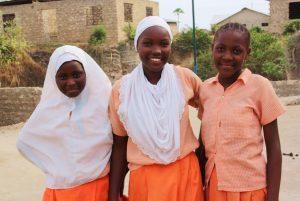 Drei junge schwarze Frauen stehen nebeneinander und lächeln fröhlich in die Kamera.