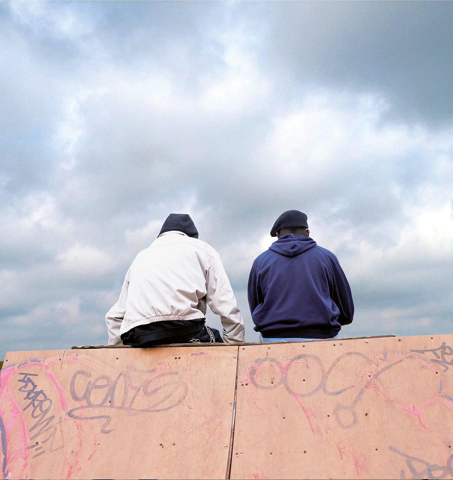 Zwei jugendliche sitzen auf einer Mauer und reden