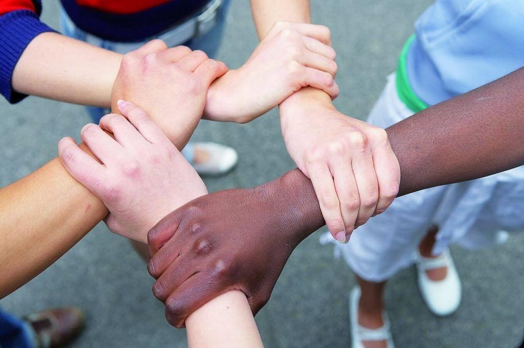 Fünf Hände mit verschiedenen Hautfarben fassen einander am Handgelenk und bilden einen Kreis.