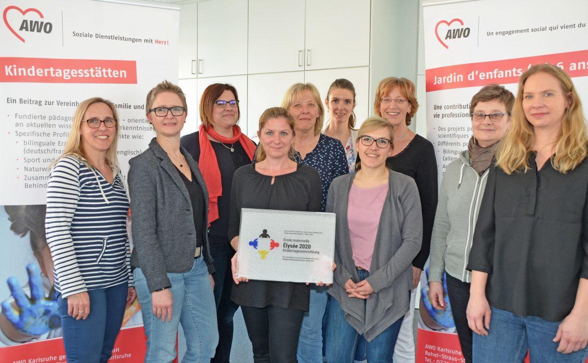 """Auf dem Bild zu sehen sind zehn junge Frauen, die im Bereich Kitas der AWO Karlsruhe arbeiten, eine von ihnen hält """"Ecoles maternelles / Bilinguale Kindertageseinrichtung – Elysée 2020"""" - die Auszeichnung für die bilinguale Arbeit in den Händen."""