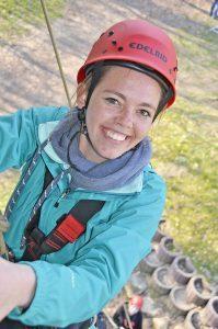 Auf dem Bild sieht man eine junge Frau, die an einem Seil an einer Wand hängt und in die Kamera lächelt.