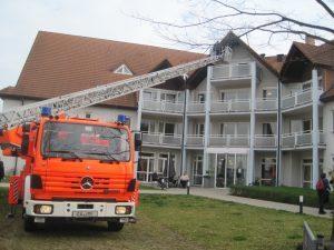 Ein Feuerwehrauto steht mit ausgefahrener Drehleiter vor dem Hanne-Landgraf-Haus