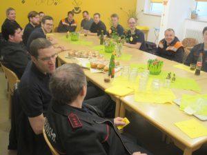 Die Mitglieder der freiwilligen Feuerwehr Grötzingen sitzen an einem gedeckten Tisch und sehen fröhlich aus.