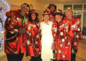 Auf dem Bild ist eine Gruppe von sechs Menschen zu sehen, die sich als Hexen verkleidet haben. Ihre Kostüme sind rot gemustert.