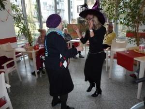 Zwei als Hexen verkleidete Menschen stehen sich gegenüber und tanzen, drumherum sitzen Seniorinnen und Senioren an Holztischen und schauen zu.