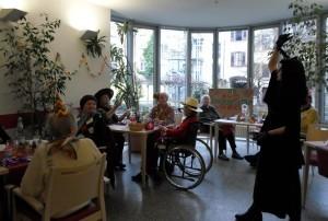 Verkleidete Seniorinnen und Senioren sitzen an einem Tisch, eine als Hexe verkleidete Frau steht danaben.