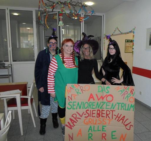 Vier verkleidete Menschen posieren vor einem Pappschild mit der Aufschrift: AWO Seniorenzentrum Karl-Siebert-Haus grüßt alle Narren