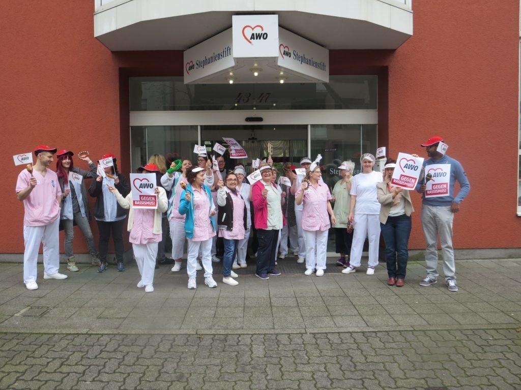 Eine Grupppe von Menschen steht vor dem AWO Seniorenzentrum Stephainienstift und hält Plakate mit dem AWO Herz Logo und der Aufschrift: AWO gegen Rassimus in die Luft. Viele schwenken AWO Fähnchen.