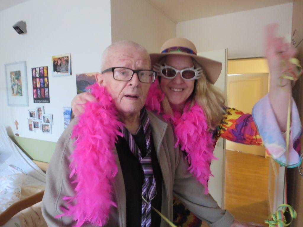 Ein Senior mit weißen Haaren trägt eine pinkfarbene Federboa um den Hals, neben ihm steht eine blonde Frau mit Hut und Sonnebrille die lächelt.