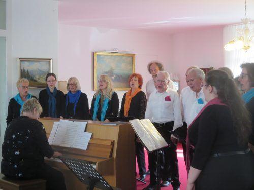 Auf dem Bild zu sehen ist ein Chor der aus Frauen und Männer besteht, es sind insgesamt 12 Personen zu sehen. Ein Mann sitzt am Klavier.