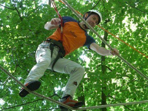Ein Mann mittleren Alters balanciert auf einem Seil im Hochseilgarten.