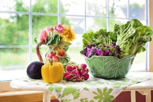 Auf einem Tisch, der vor einem Fenster mit Blick ins Grüne steht, liegen eine Aubergine, eine gelbe Paprika, rote Radieschen und eine grüne Schale mit Salat. Außerdem steht noch eine Vase mit bunten Blumen auf dem Tisch.