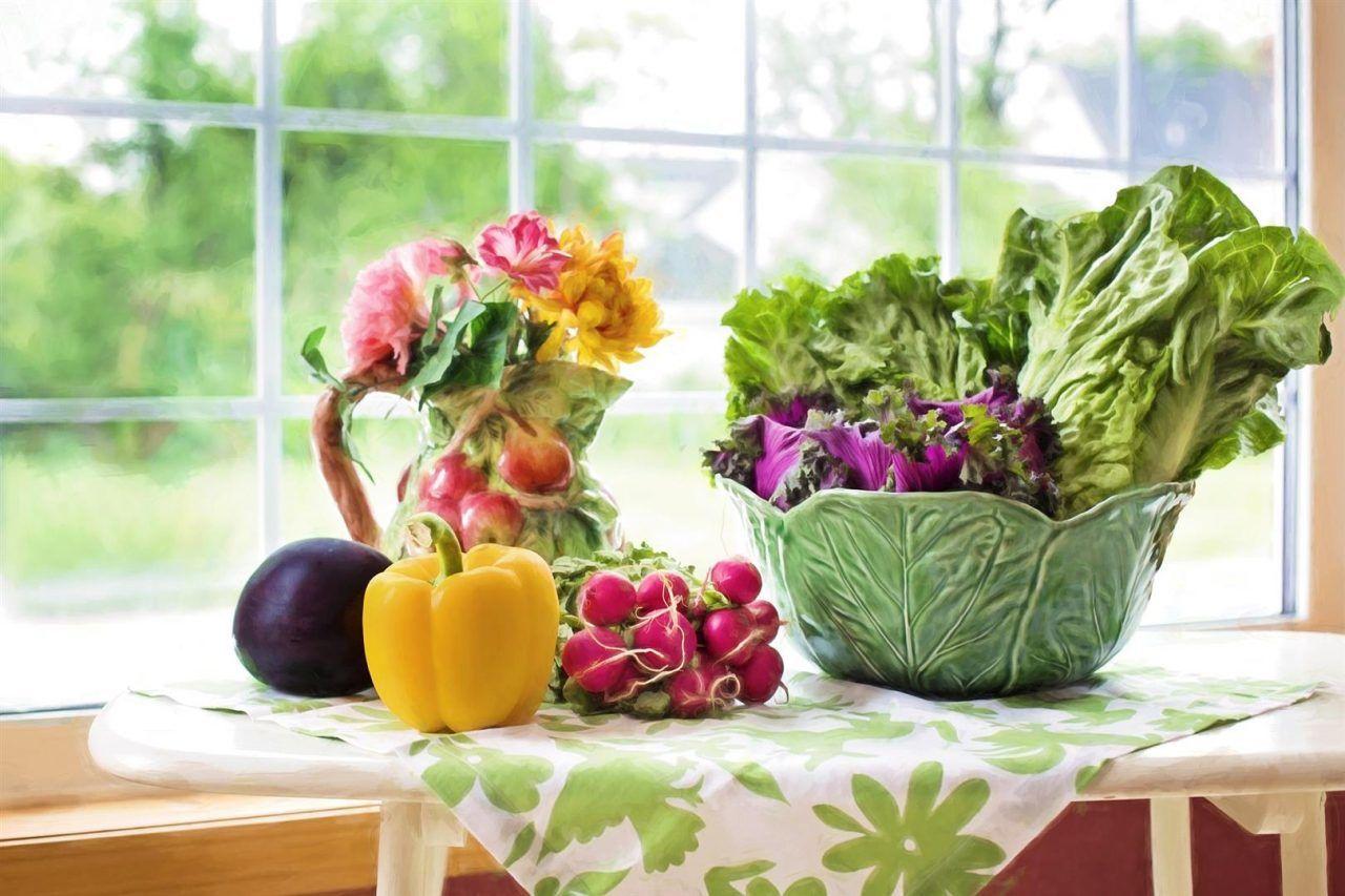 Gemüse liegt auf einem Tisch vor einem Fenster.
