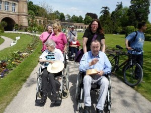 Auf dem Bild sind ein Mann und eine Frau zu sehen, die im Rollstuhl sitzen und von zwei Frauen durch den Botanischen Garten in Karlsruhe geschoben werden.