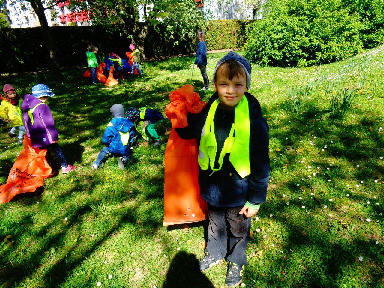 Auf dem Bild ist ein kleiner Junge zu sehen, der eine Mülltüte festhält.