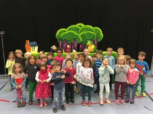 Eine Gruppe von KiTa-Kindern steht vor einer Theaterkulisse aus grünen Bäumen.