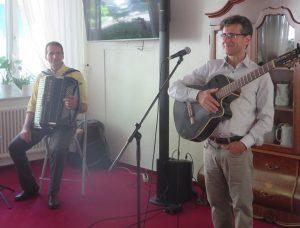 Auf dem Bild sind ein Mann am Akkordeon und ein Mann mit einer Gitarre zu sehen.