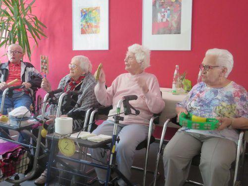 Auf dem Bild sind drei Seniorinnen zu sehen, die auf Stühlen sitzen und in die Hände klatschen.
