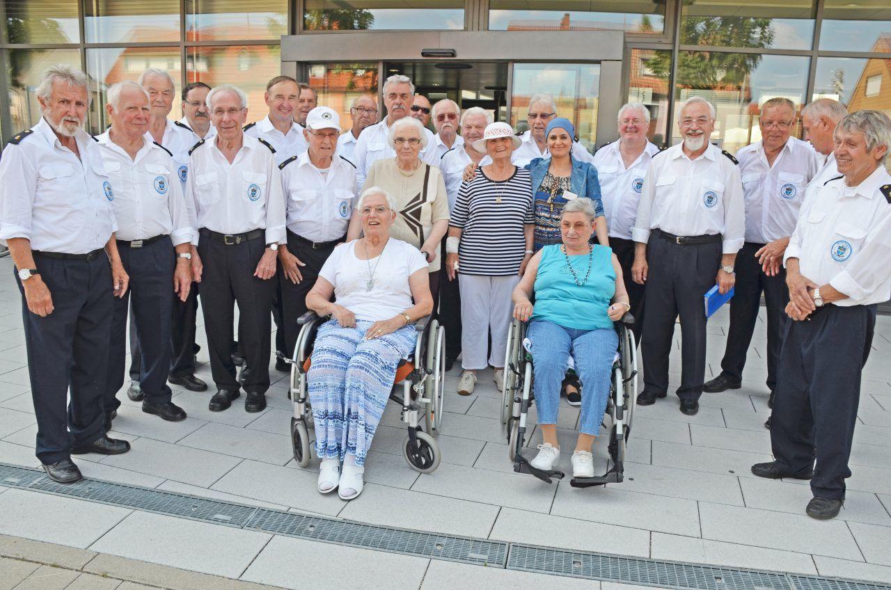 Die Marine Singers Rheinstetten und vier Seniorinnen lächeln in die Kamera.