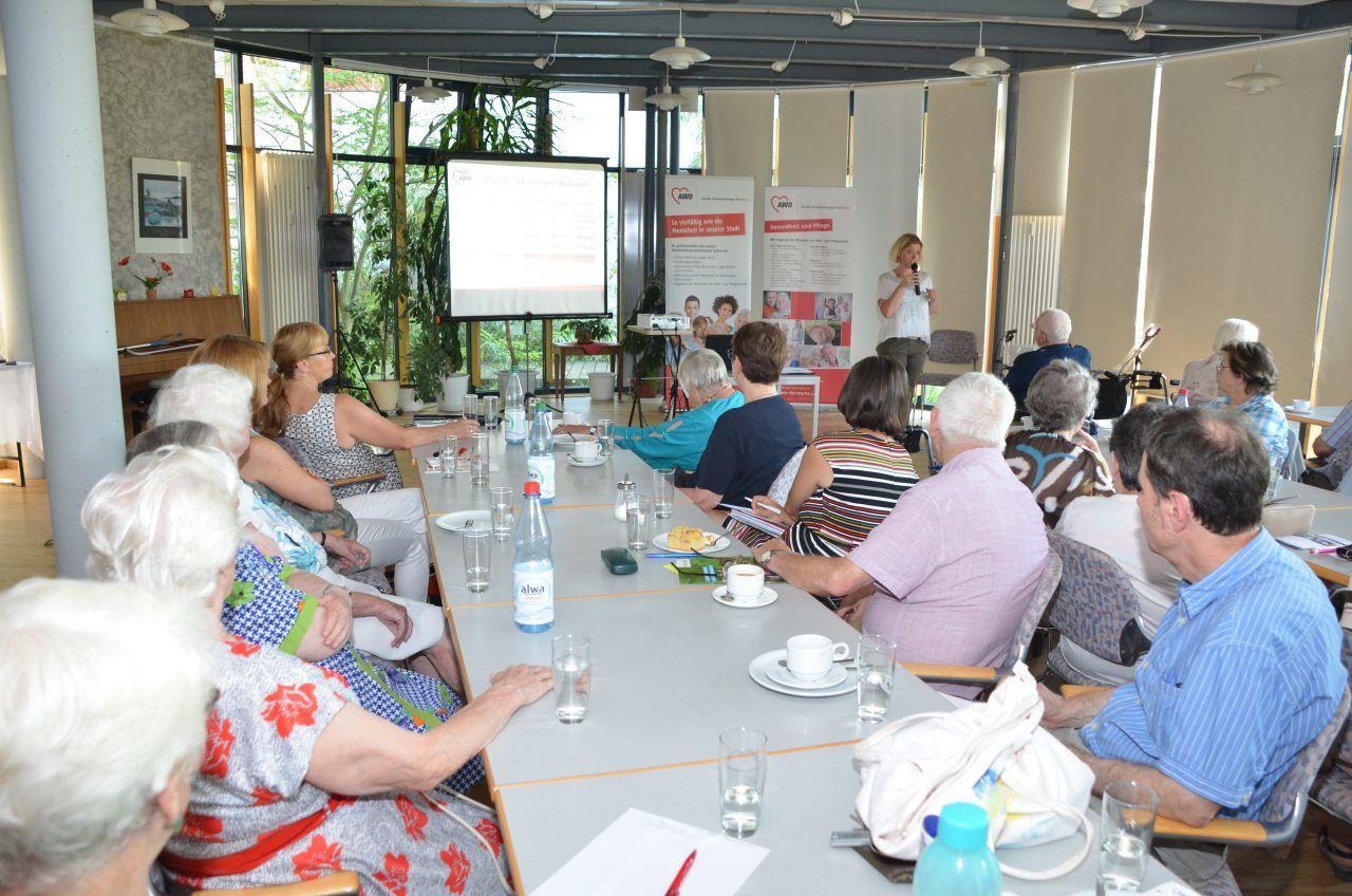 Viele Senioren sitzen an einem langen Tisch und hören sich einen Vortrag an.