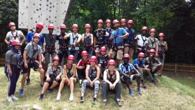 Frauen und Männer tragen Helme und stehen vor einer Kletterwand.