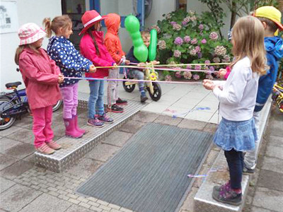 Kinder stehen sich gegenüber und spielen Gummi-Twist.