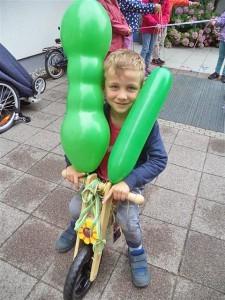 Ein fünfjähriger Junge sitzt auf einem Laufrad an dem zwei grüne Luftballons befestigt sind.