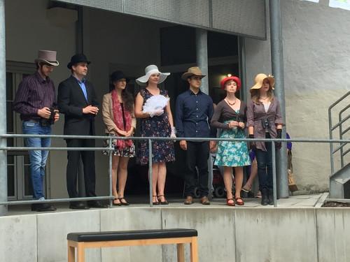 Eine Gruppe von jungen Menschen steht auf einem Balkon und ist verkleidet.