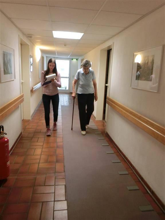 Eine junge Frau macht sich Notizen und läuft mit einer Seniorin in einem Flur einen Gang entlang.