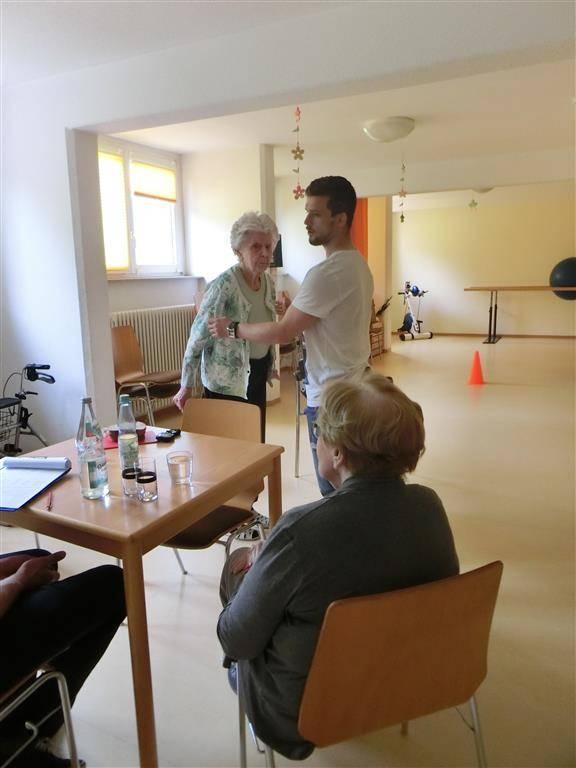 Eine Seniorin steht vor einem jungen Mann, der mit ihr Sportübungen macht.