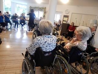 Zwei grauhaarige Frauen sitzen im Rollstuhl und hören Musikern beim Musizieren zu.