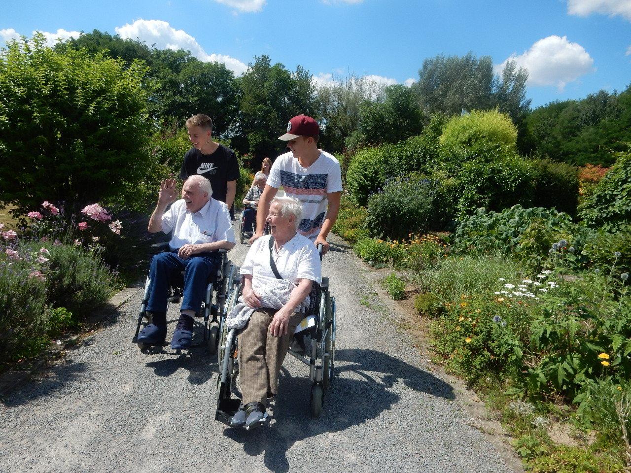 Zwei Senioren werden von zwei jungen Männern mit dem Rollstuhl durch eine blühende Landschaft geschoben.