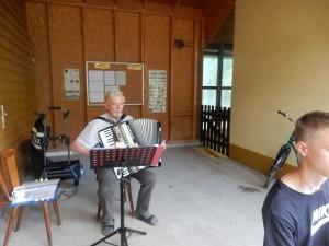 Ein grauhaariger Mann spielt Akkordeon.