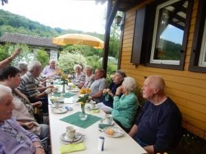 Viele grau- und weißhaarige Menschen sitzen an einem gedeckten Tisch.