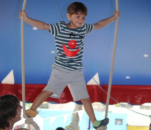 Ein Junge steht auf einer Schaukel in einem Zirkuszelt.