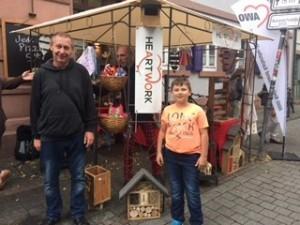 Ein Mann und sein Sohn stehen vor dem Stand des AWO Arbeitsprojektes mit den Handgefertigten Produkten.