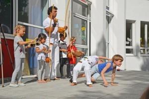 Fünf Kinder machen zusammen mit einem Trainer Capoeira.