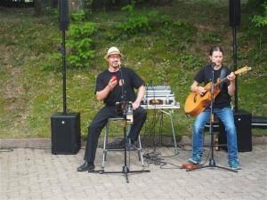 Ein Mann am Mirkophon und ein Mann mit Gitarrre