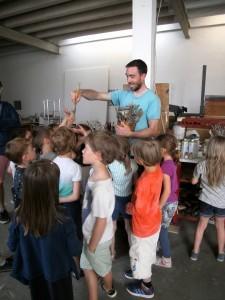Ein Mann verteilt Pinsel an Kinder.
